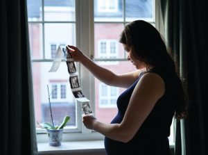 A pregnant woman looking at scans of her unborn infant by a window. Roche Diagram healthcare magazine publications